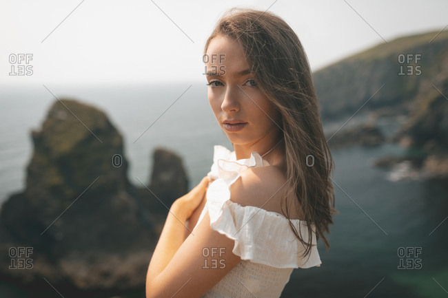 Portrait of beautiful woman standing near the sea on a breezy day