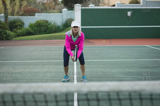 Portrait senior woman playing tennis in tennis court