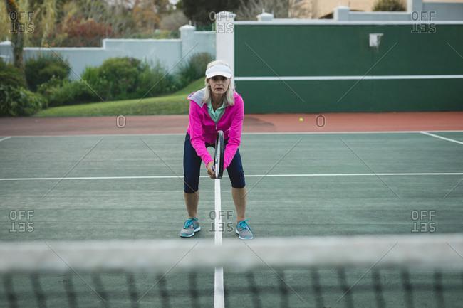 Portrait senior woman playing tennis in tennis court