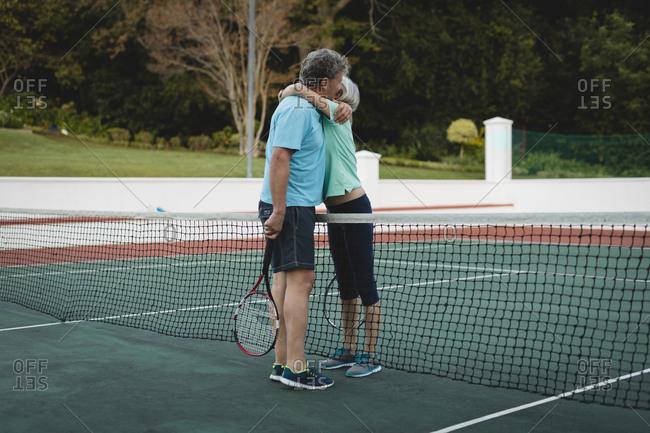 Senior couple hugging in tennis court