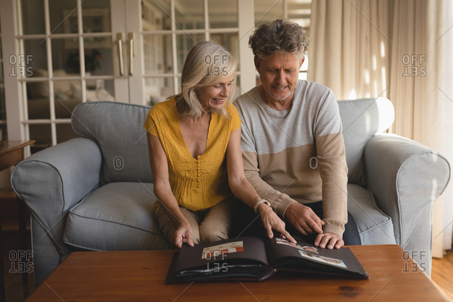 Senior couple looking at photo album at home