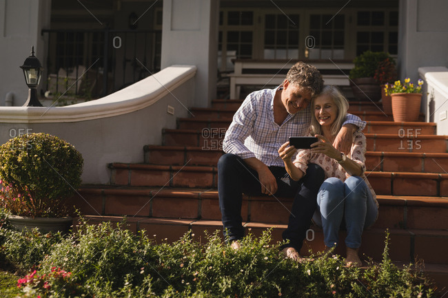 Senior couple using mobile phone on the entrance steps at home