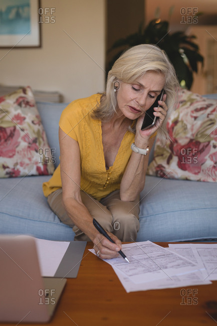 Senior woman talking on mobile phone while checking bills at home