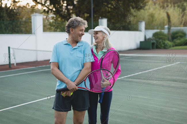 Smiling senior couple looking each other in tennis court