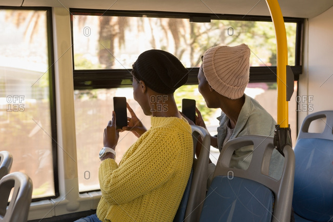 Twins siblings clicking photos with mobile phone in the bus