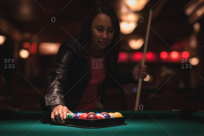 Woman arranging snooker balls in triangle rack at night club