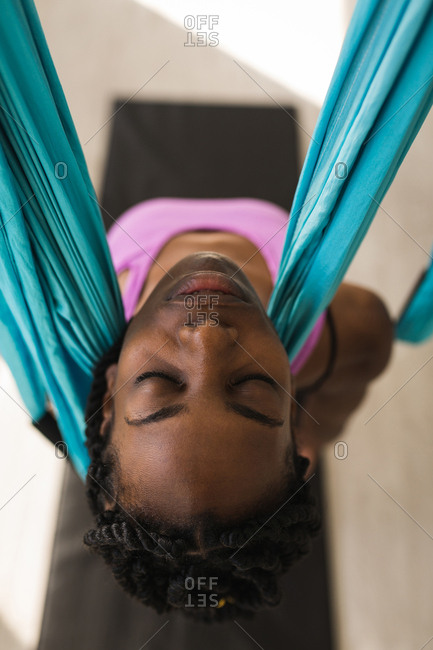 Woman exercising on swing sling hammock at fitness studio