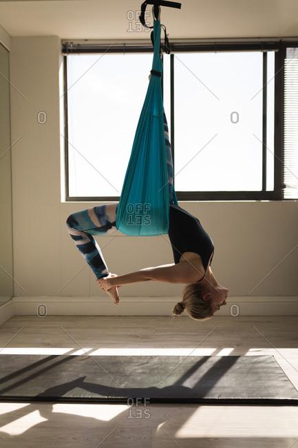 Woman exercising on swing sling hammock at fitness studio