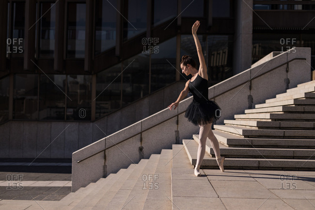 Woman performing ballet on the steps in the city