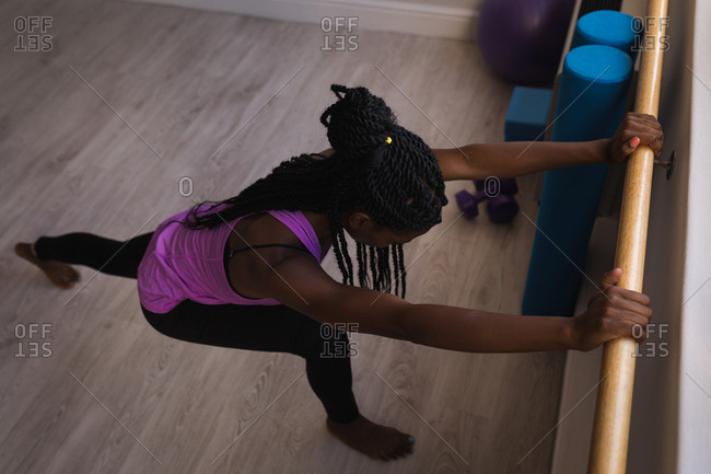 Woman performing barre exercise in fitness studio