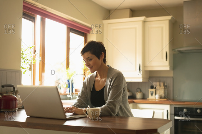 Woman using laptop in the kitchen at home