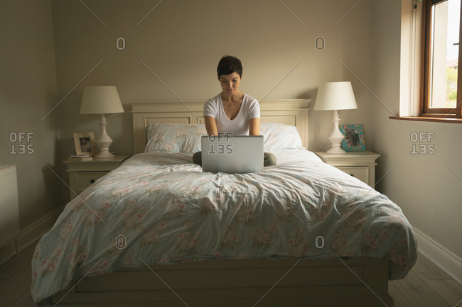 Woman using laptop on bed in bedroom at home
