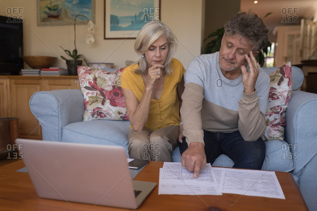 Worried senior couple discussing bills together at home
