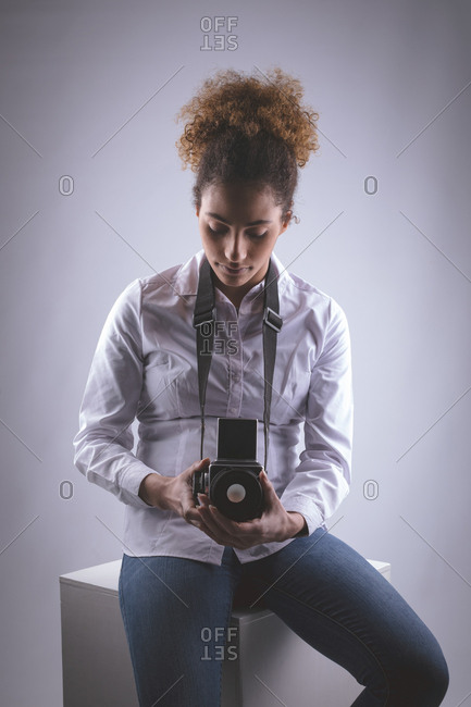Young female photographer clicking photos in photo studio