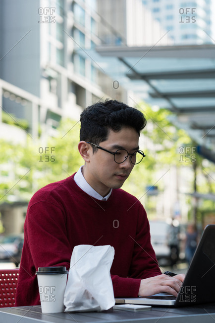 Young man using laptop at outdoor cafe