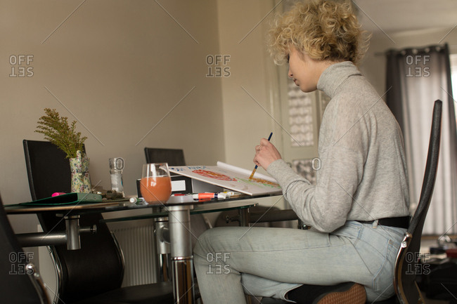 Female blogger coloring a sketch at home