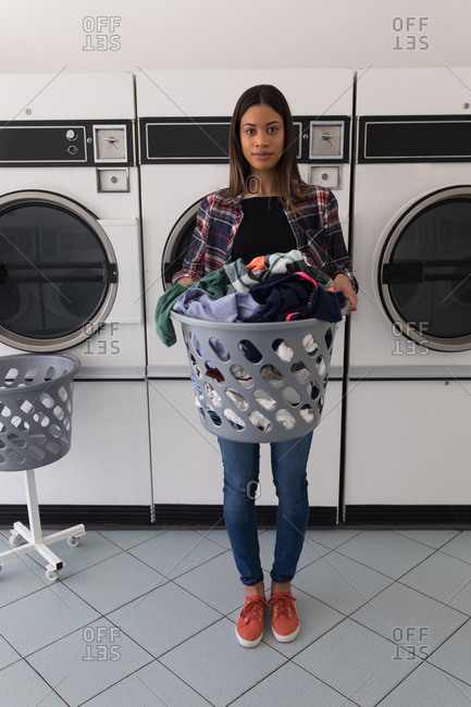 Portrait of woman carrying laundry basket at Laundromat
