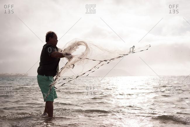 Fisherman throwing fishing net on the beach at dusk