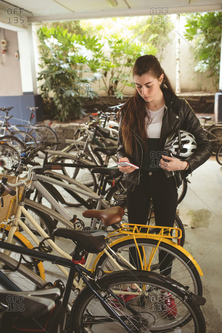 Beautiful woman using mobile at bicycle stand
