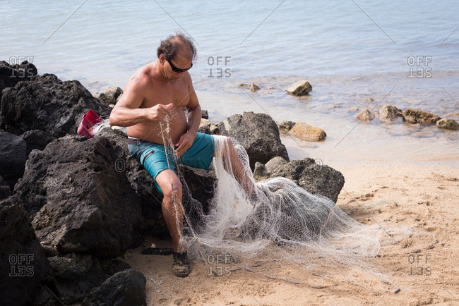 Fisherman holding fishing net on the beach