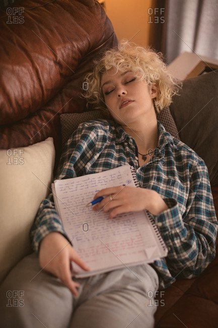 Young woman sleeping in living room at home