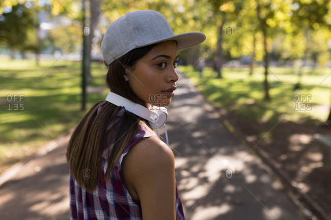 Woman with headphones looking over shoulders in the park