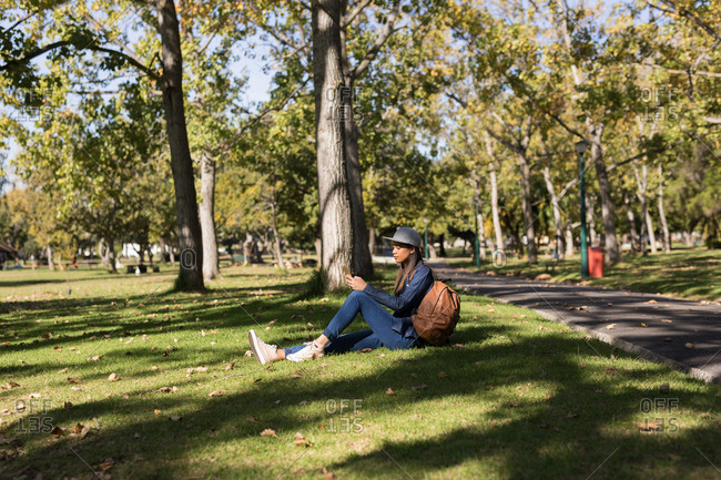 Young woman sitting in the park using mobile phone