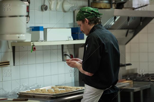 Male chef preparing dough ball in kitchen at restaurant