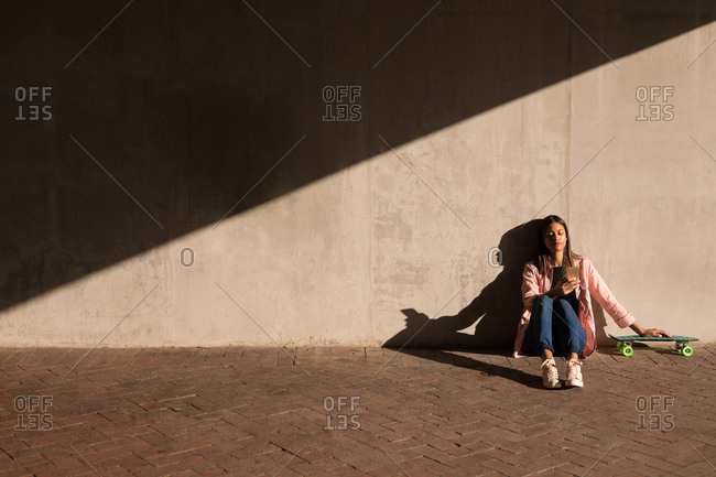 Woman with mobile phone and skateboard sitting against a wall on a sunny day
