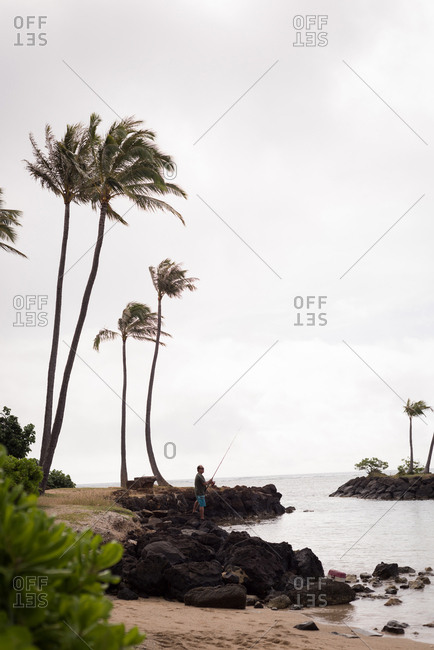 Fisherman fishing alone on a beach