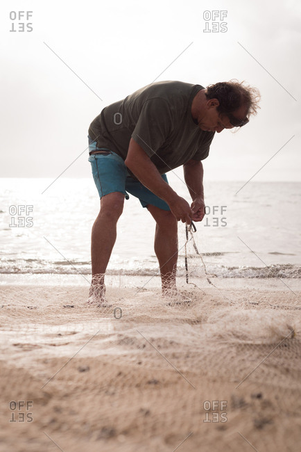 Mature fisherman holding fishing net on the beach