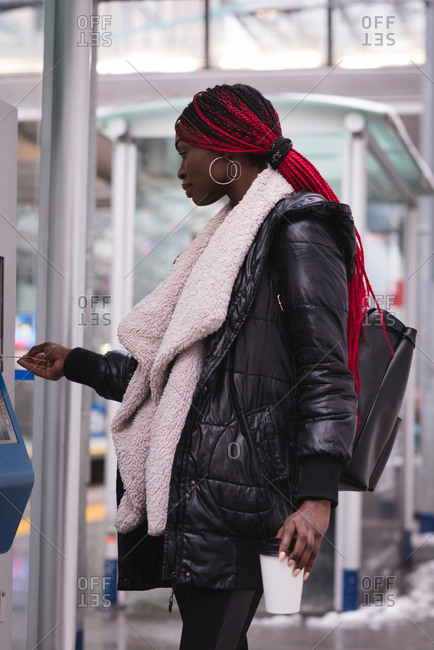 Young woman using ticket vending machine at station
