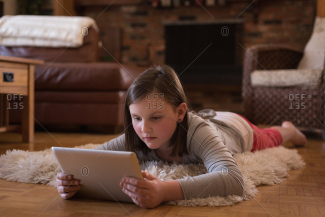 Girl using digital tablet in living room at home