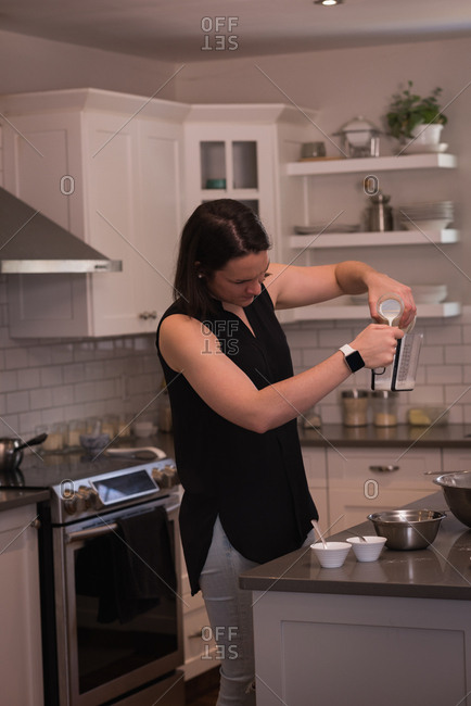Woman pouring mug into jug in kitchen at home