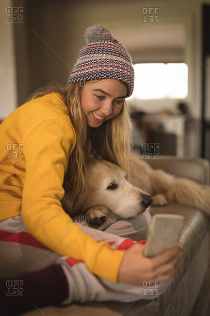 Girl taking selfie with dog in living room at home