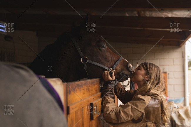Teenage girl petting a horse in the ranch