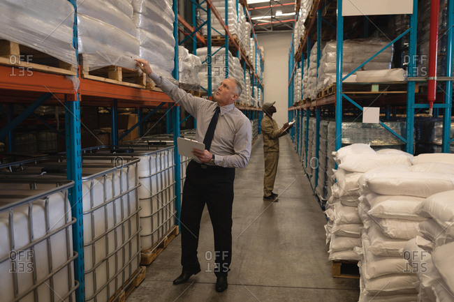 Male manager checking stocks in warehouse