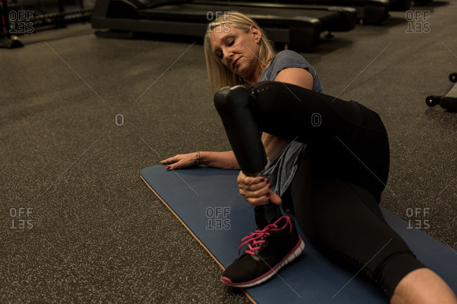 Disabled woman performing stretching exercise in the gym