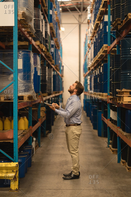 Male manager using laptop while checking stocks in warehouse