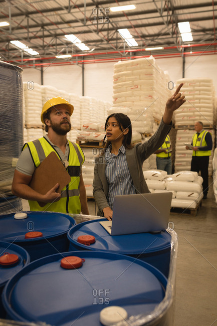Staff interacting with each other over laptop in warehouse