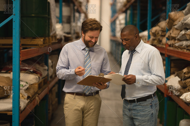 Male managers discussing over clipboard in warehouse