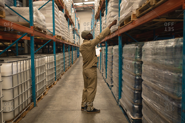 Male worker checking stocks in warehouse