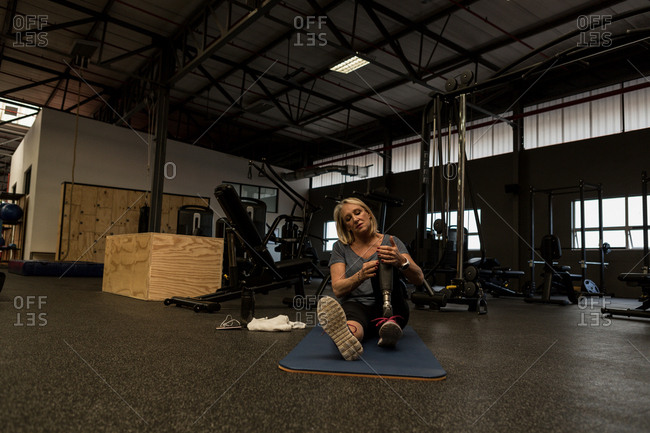 Disabled mature woman with prosthetic leg in the gym