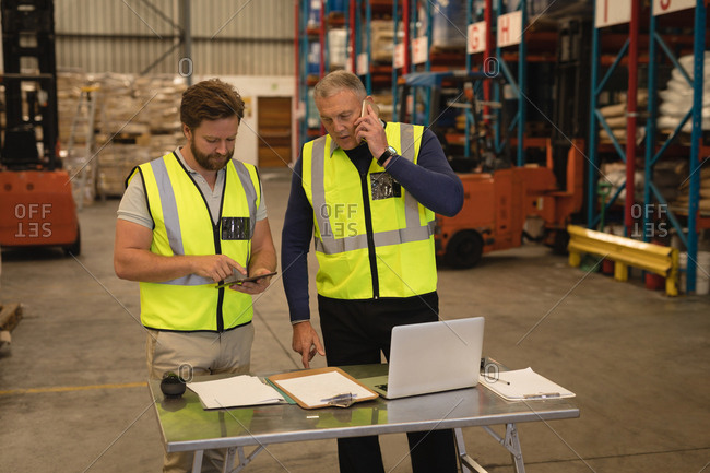 Male supervisors talking on mobile phone and using digital tablet in warehouse