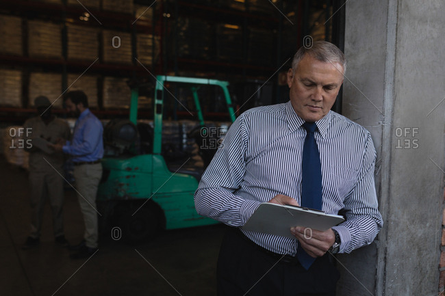 Male manager writing on a clipboard in warehouse