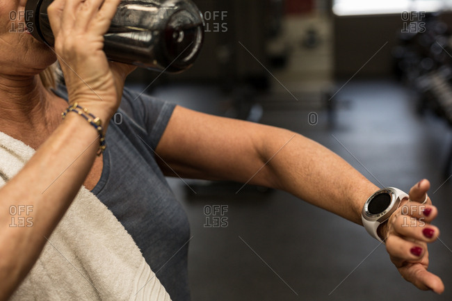 Mid section of mature woman checking time while drinking water in the gym