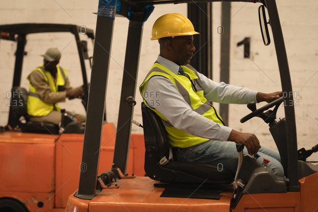 Male worker driving forklift in warehouse