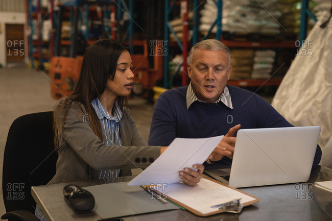 Staff interacting with each other over documents in warehouse