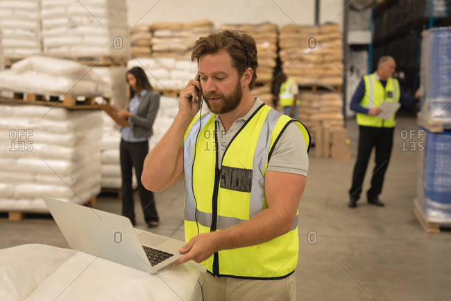 Male supervisor talking on mobile phone while using laptop in warehouse
