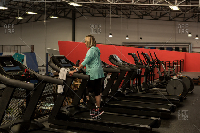 Disabled mature woman exercising on treadmill in the gym
